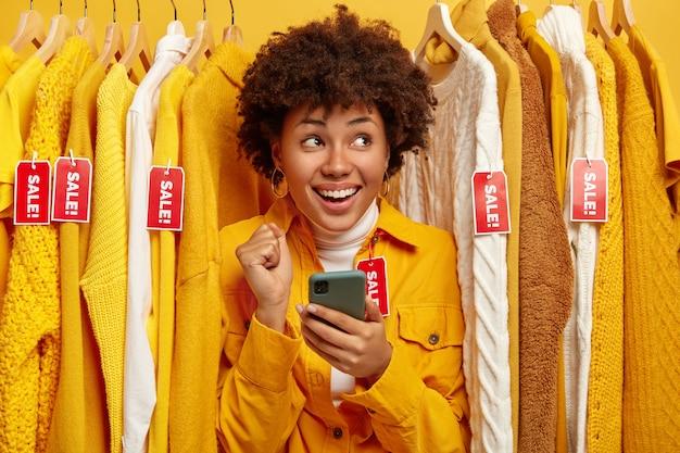 Sprzedaż, Moda, Rabaty I Koncepcja Zakupów Online. Uradowana Ciemnoskóra Kobieta Wybiera Ubrania W Sklepie Odzieżowym, Cieszy Się Z Wielkich Wyprzedaży, Trzyma Telefon Darmowe Zdjęcia