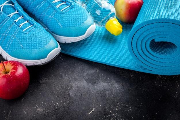 Sprzęt sportowy buty sportowe, mata do jogi, jabłka, butelka wody. Premium Zdjęcia