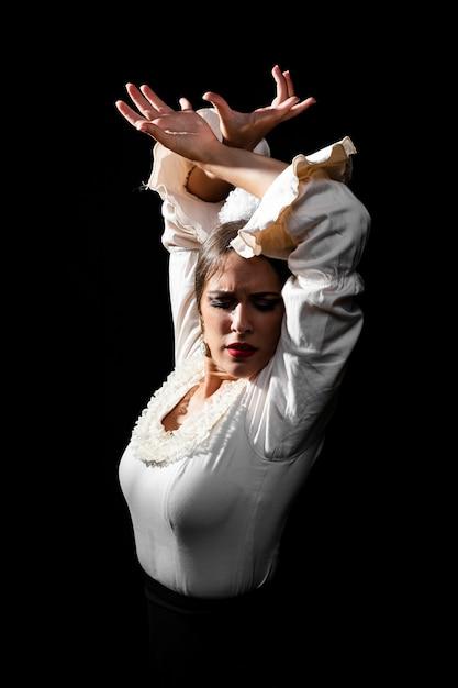 Średni Strzał Flamenca Podnosząc Ręce Na Czarnym Tle Darmowe Zdjęcia