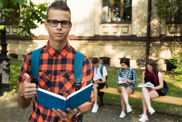 Średni strzał portret highschool chłopiec trzyma otwartą książkę Darmowe Zdjęcia
