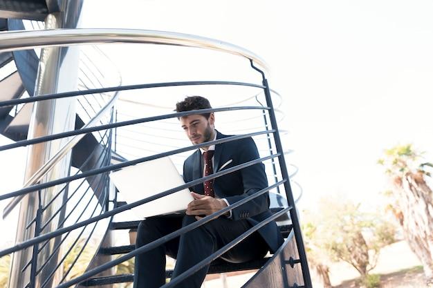 Średni strzał pracującego człowieka siedzącego na schodach Darmowe Zdjęcia