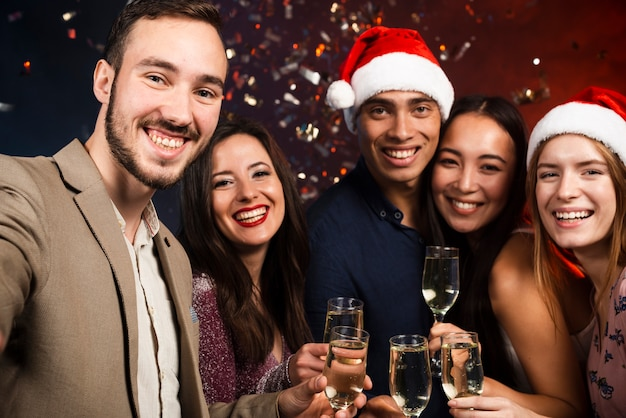 Średni strzał przyjaciół na imprezie noworocznej z kieliszkami do szampana Darmowe Zdjęcia