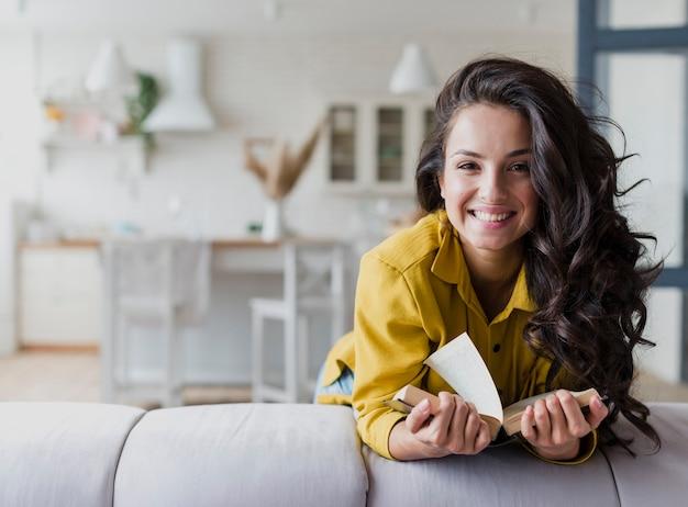 Średni Strzał Szczęśliwa Brunetki Kobieta Z Książką Premium Zdjęcia