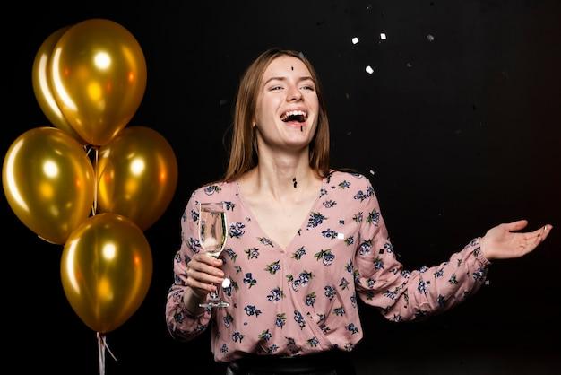 Średni strzał uśmiechnięta kobieta przy nowym rokiem bawi się Darmowe Zdjęcia