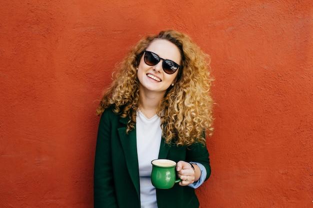 Średni zbliżenie zadowolonej ładnej kobiety z kręconymi włosami w okularach przeciwsłonecznych i kurtce. Premium Zdjęcia