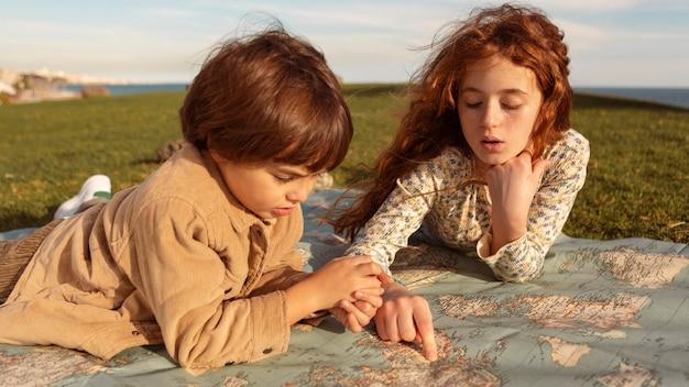 Średnie Ujęcia Dzieci Patrzące Na Mapę Darmowe Zdjęcia