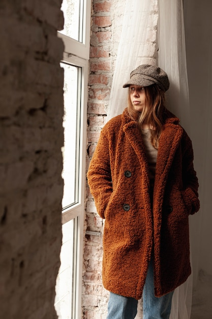 Średnio strzał dziewczyna z ciepłym płaszczem i kapeluszem Darmowe Zdjęcia