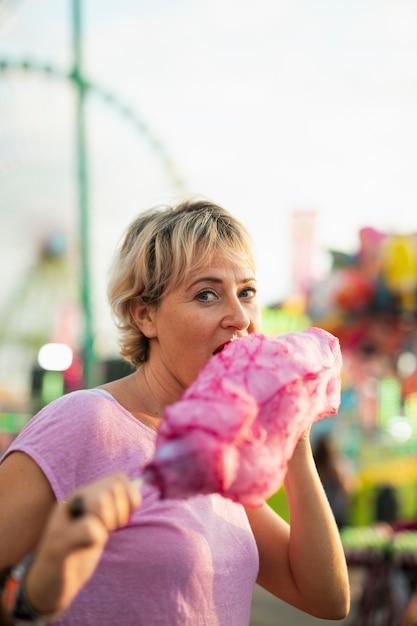 Średnio strzał kobieta jedzenia waty cukrowej Darmowe Zdjęcia