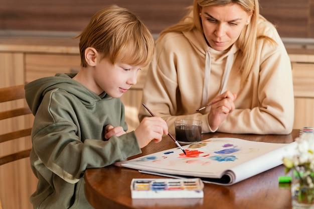 Średnio Strzał Kobieta Oglądając Malowanie Dzieciaka Darmowe Zdjęcia