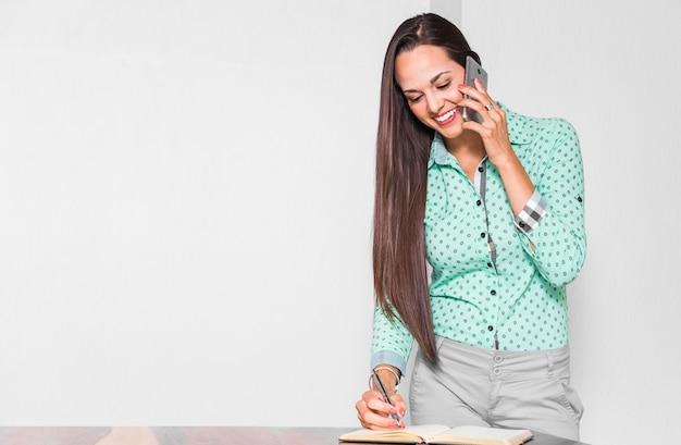 Średnio strzał kobieta robi jej pracę w biurze Darmowe Zdjęcia