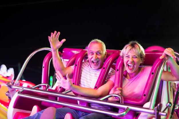 Średnio strzał szczęśliwa para w przejażdżce rozrywki Darmowe Zdjęcia