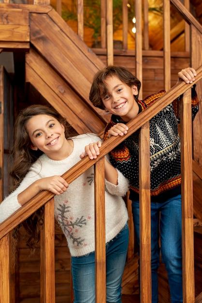 Średnio strzał szczęśliwe dzieci stojące na schodach Darmowe Zdjęcia