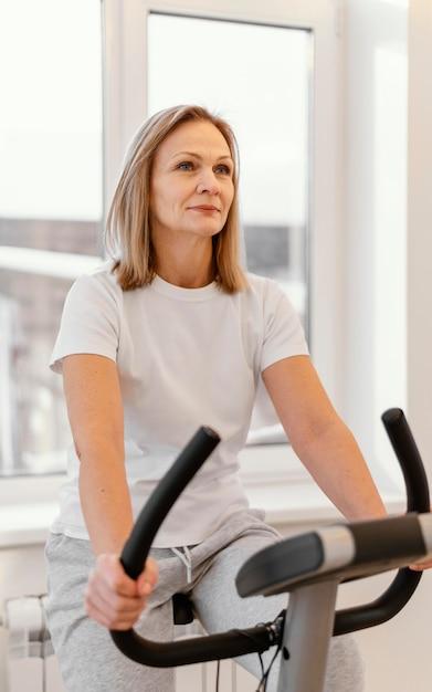 Średnio Strzał Uśmiechnięta Kobieta Na Rowerze Spin Premium Zdjęcia