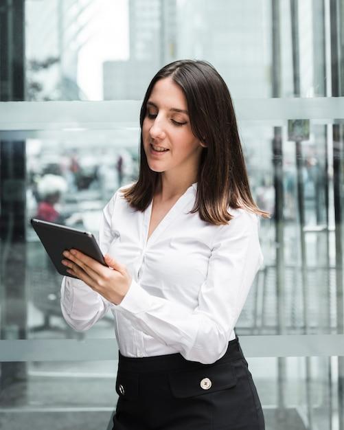 Średnio strzał uśmiechnięta kobieta patrząc na jej tabletki Darmowe Zdjęcia