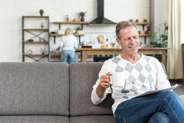 Średnio strzał uśmiechnięty mężczyzna czyta na kanapie Darmowe Zdjęcia