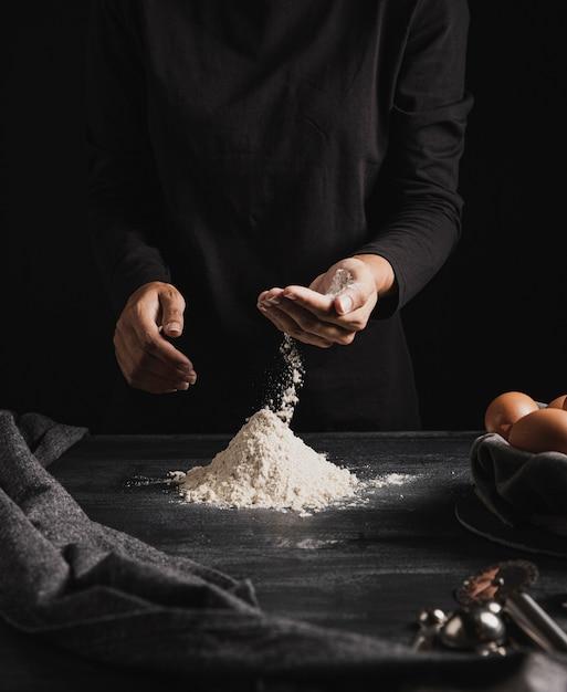 Średnio strzałowe ręce piekarza mieszające mąkę Darmowe Zdjęcia