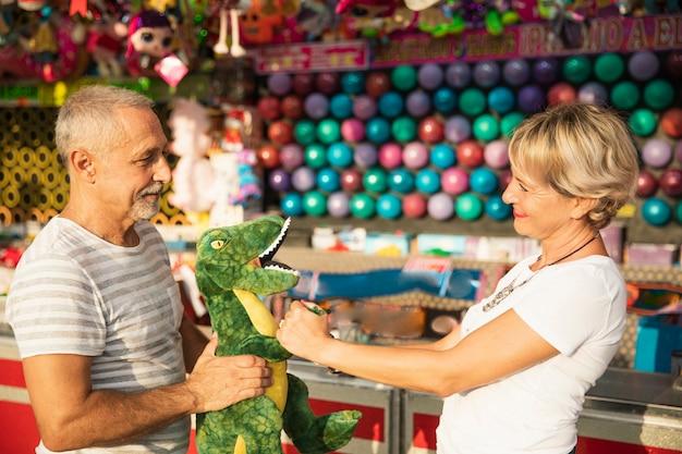 Średnio strzelający ludzie z zabawką dinozaura Darmowe Zdjęcia