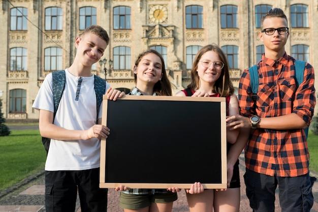 Średnio strzelający nastolatkowie trzyma blackboard Darmowe Zdjęcia