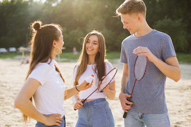 Średnio strzelający uśmiechnięci przyjaciele z rakietkami do badmintona Darmowe Zdjęcia