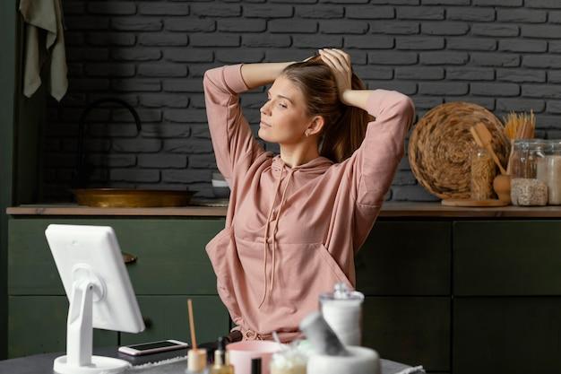 Średnio Ujęta Kobieta Wiążąca Włosy W Pomieszczeniu Darmowe Zdjęcia