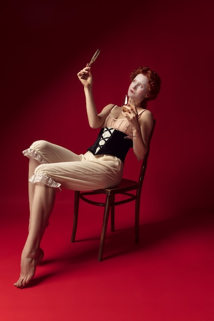 Średniowieczna Ruda Młoda Kobieta Jako Księżna W Czarnym Gorsecie I Nocnych Ubraniach Siedzi Na Czerwono Darmowe Zdjęcia