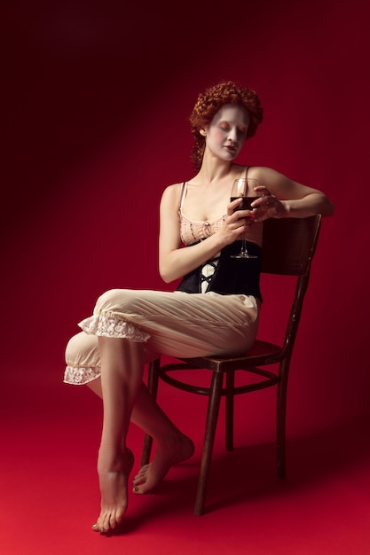 Średniowieczna Rudowłosa Młoda Kobieta Jako Księżna W Czarnym Gorsecie I Nocnych Ubraniach Siedzi Na Krześle Na Czerwonej Przestrzeni Z Lampką Wina Darmowe Zdjęcia