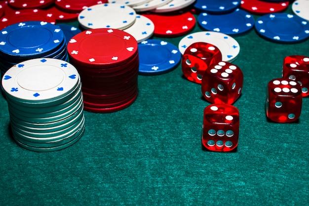 Stack żetonów I Czerwone Kostki Na Zielonym Stole Pokerowym Premium Zdjęcia