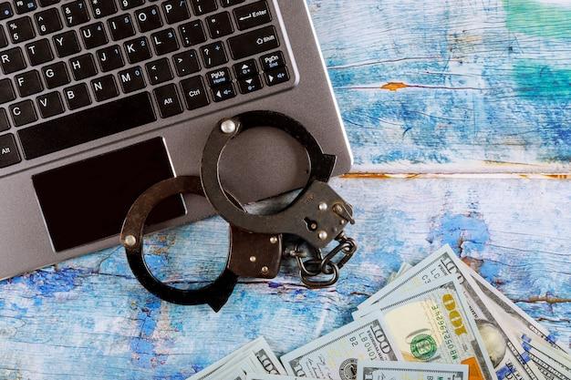Stalowe kajdanki policyjne na stosie stu dolarowych banknotów z klawiaturą komputerową, technologia cyberprzestępczości internet Premium Zdjęcia