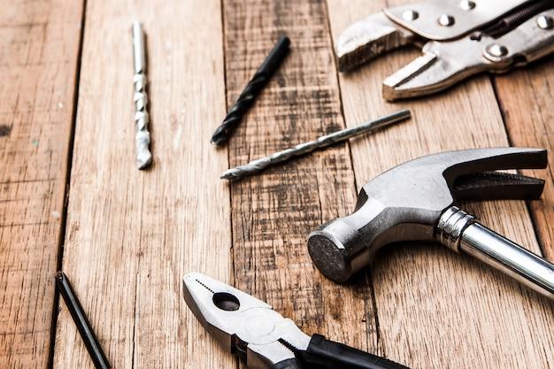 Stalowe szczypce i młotek cieśla narzędzie na tle drewna Premium Zdjęcia