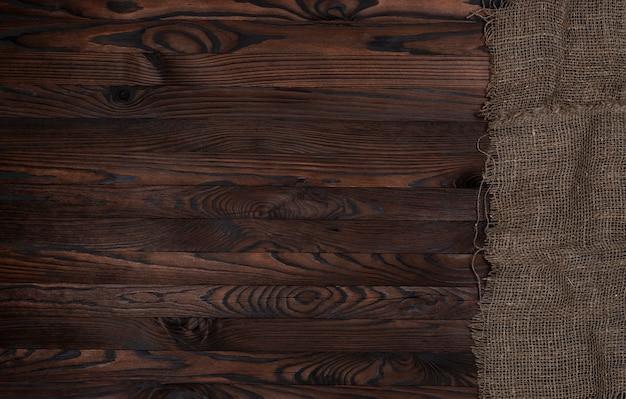Stara burlap tkaniny pielucha na brown drewnianym tle, odgórny widok Premium Zdjęcia