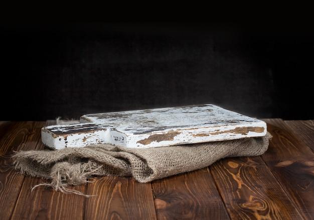 Stara drewniana deska do krojenia z płótnie obrus Premium Zdjęcia