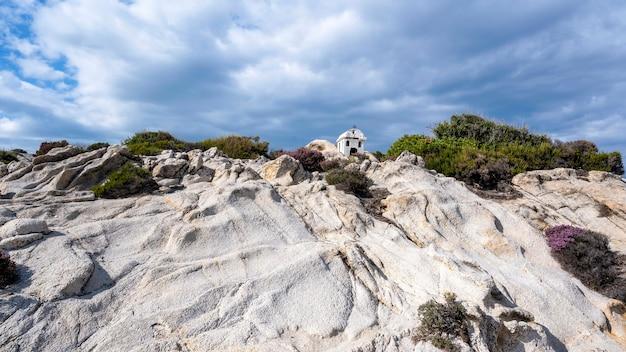 Stara I Mała Kapliczka Położona Na Skałach W Pobliżu Wybrzeża Morza Egejskiego, Dookoła Krzaki, Zachmurzone Niebo, Grecja Darmowe Zdjęcia