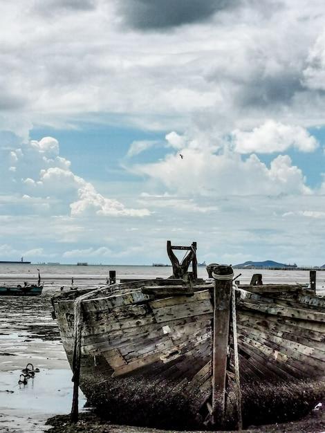 Stara i uszkodzona łódź na plaży Premium Zdjęcia