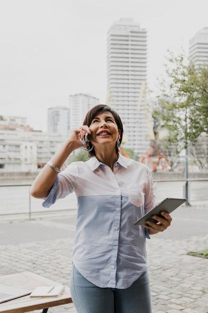 Stara kobieta opowiada na telefonie na miastowym tle Darmowe Zdjęcia