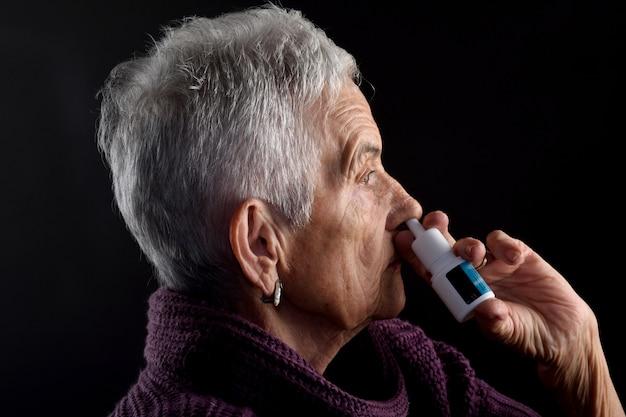 Stara kobieta z sprayem do nosa Premium Zdjęcia