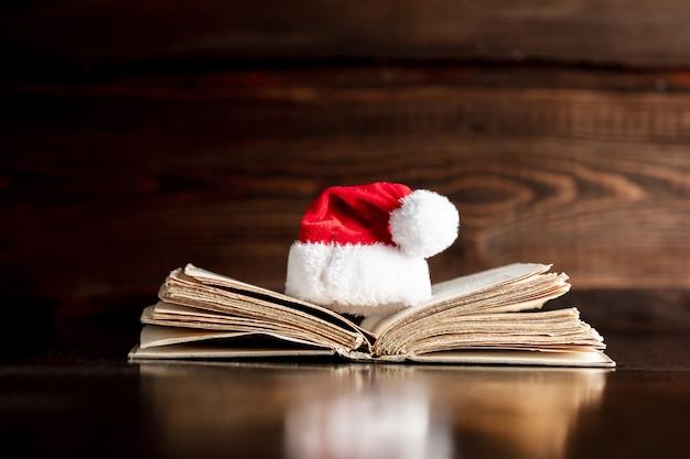 Stara książka i boże narodzenie kapelusz na drewnianym stole Premium Zdjęcia