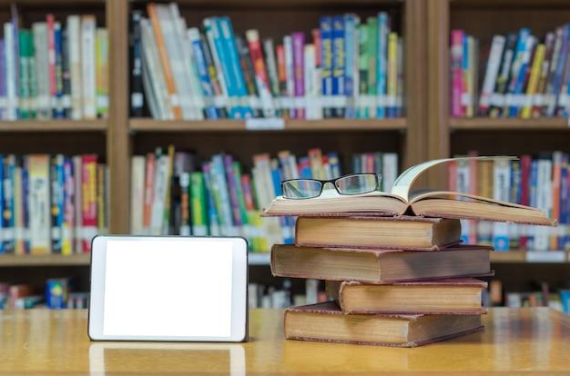 Stara książka na biurku w bibliotece z tabletu i okulary Premium Zdjęcia