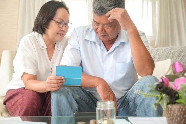 Stare azjatyckie kobiety i mężczyźni siedzą na kanapie, robią plany finansowe. Premium Zdjęcia