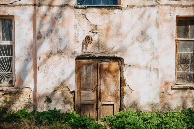 Stare Drewniane Drzwi Na Zwietrzałej I Zapadającej Się ścianie. Premium Zdjęcia