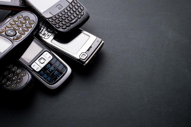 Stare I Przestarzałe Telefony Komórkowe Na Czarnym Tle. Premium Zdjęcia