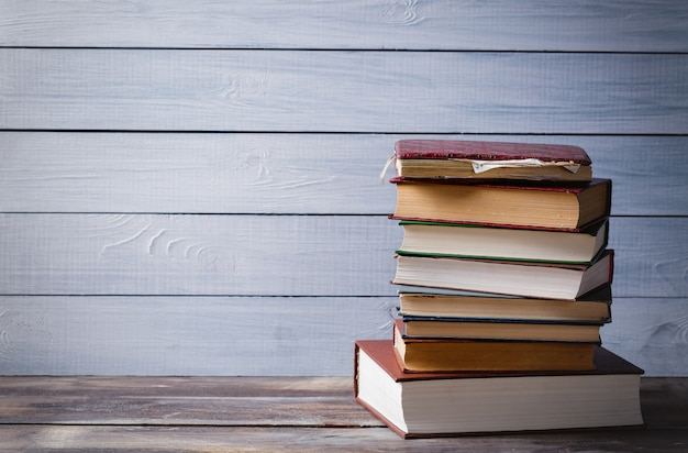 Stare książki na błękitnym drewnianym tle Premium Zdjęcia