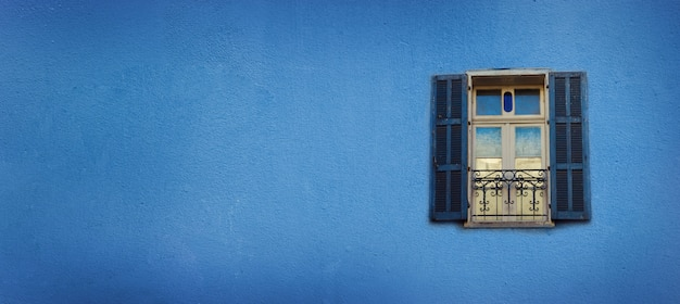 Stare Niebieskie Malowane Okna Na Betonowej ścianie. Baner Z Miejsca Na Kopię. Koncepcja Pop-artu, Okno W Stylu Greckim Premium Zdjęcia