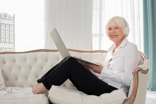 Starej kobiety obsiadanie na kanapie z hełmofonami i laptopem Darmowe Zdjęcia