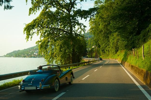 Starsi Ludzie W Retro Samochód Jadący Po Drodze Z Pięknym Letnim Krajobrazem. Szwajcarski. Darmowe Zdjęcia