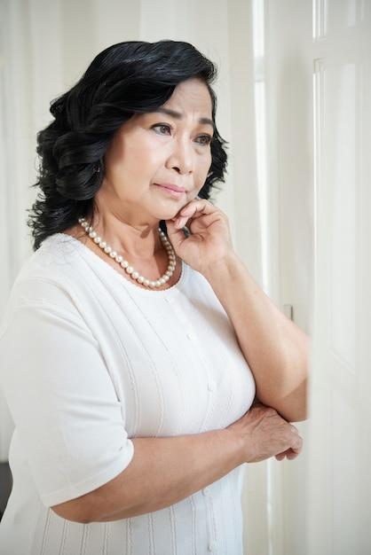 Starsza Azjatycka Kobieta Stoi Okno W Domu I Patrzeje Daleko Od Darmowe Zdjęcia
