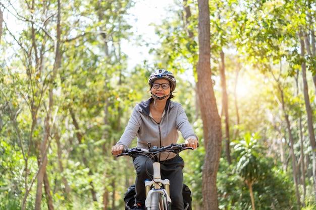 Starsza Azjatykcia Kobiety Jazda Jechać Na Rowerze W Parku Premium Zdjęcia