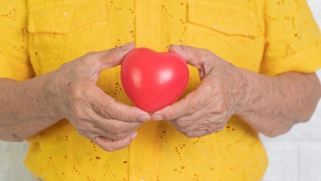 Starsza Azjatykcia Kobiety Mienia Czerwieni Serce. Koncepcja Samotności I Powinna Być Pod Opieką Dzieci I Bliskich Premium Zdjęcia