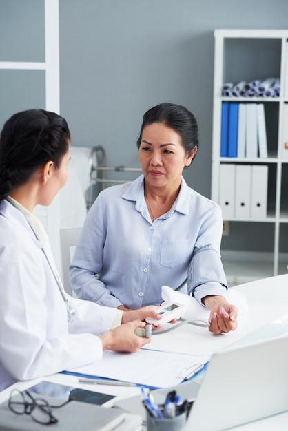 Starsza kobieta azji siedzi w gabinecie lekarskim i mierzone ciśnienie krwi Darmowe Zdjęcia