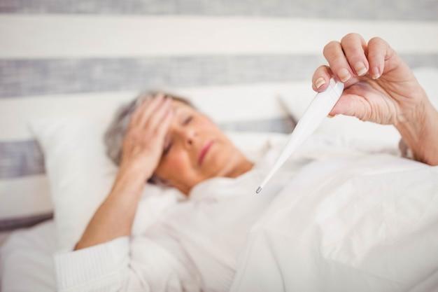 Starsza Kobieta Cierpi Na Gorączkę Sprawdzającą Temperaturę Na Termometrze Premium Zdjęcia