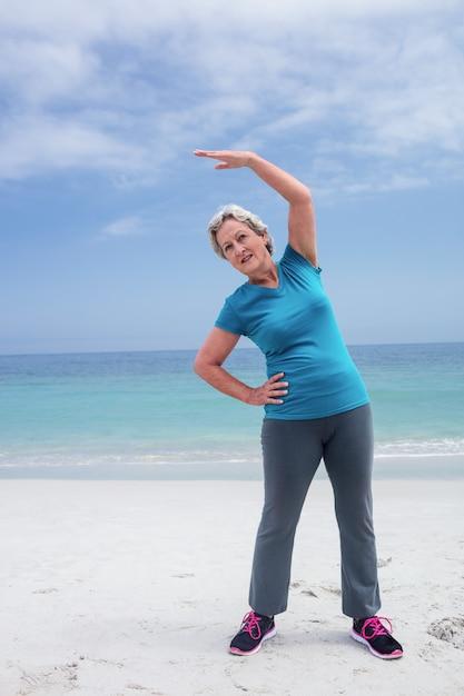 Starsza kobieta ćwiczy na plaży Premium Zdjęcia